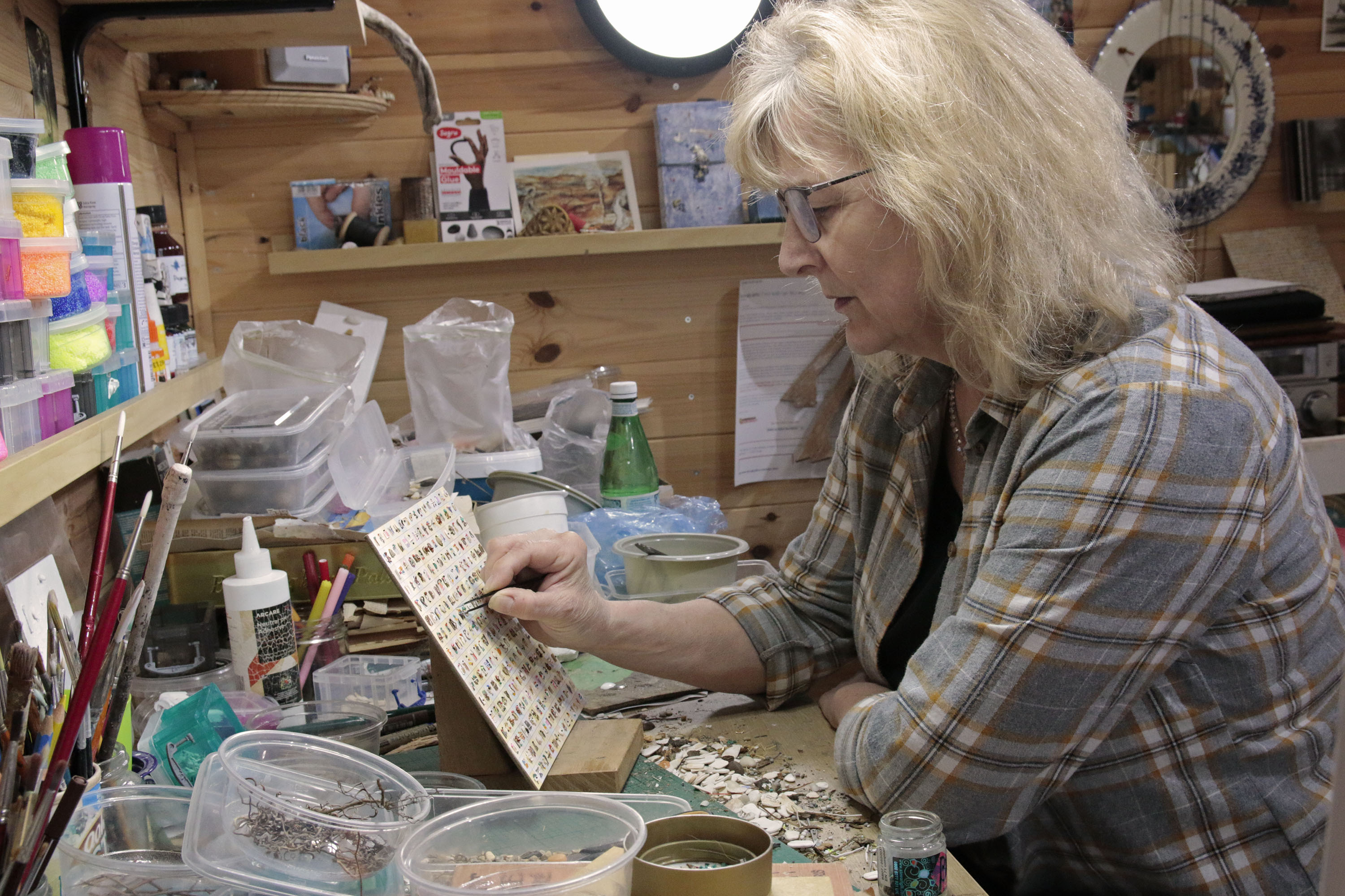 Artist Helen Murray working at her desk on a delicate, small piece.